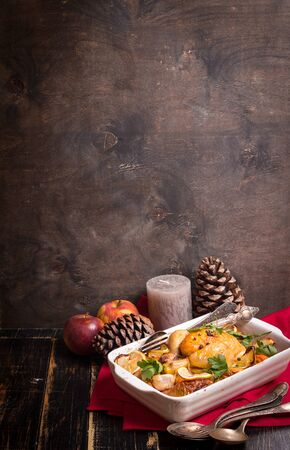 Roasted chicken. Christmas food background. Rustic celebration table with roasted chicken, vegetables, apples, decorated with candles, vintage cutlery. Christmas/Thanksgiving dinner. Space for text