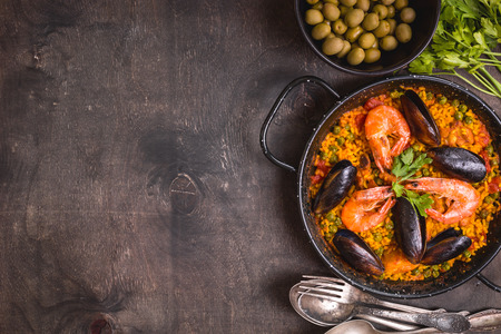 Paella background, space for text. Paella in black pan with saffron rice, peas, shrimps, mussels, squid, meat. Seafood paella, traditional spanish dish. Paella on rustic black wooden table. Top view