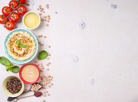 Bowl with hummus, chickpea, tahini, olive oil, sesame seeds, cherry tomatoes and herbs on white rustic wooden background. Space for text. Food frame. Middle eastern cuisine. Top view. Hummus background