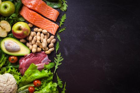 신선한 야채, 과일, 생선, 고기, 검은 분필 보드 배경에 견과류. ? 아울렛, 아보카도, 사과, 토마토, 연어, 쇠고기, 시금치, 허브. 다이어트  건강  고식