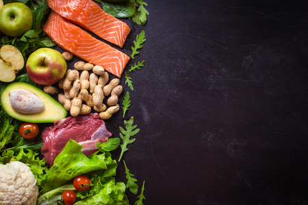 Fresh vegetables, fruits, fish, meat, nuts on black chalk board background. ?auliflower, avocado, apples, tomatoes, salmon, beef, spinach, herbs. Diet/healthy/paleo food. Ingredients. Space for text