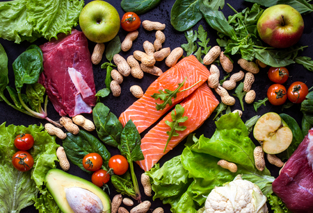 Fresh vegetables, fruits, fish, meat, nuts on black chalk board background. ?auliflower, avocado, apples, tomatoes, salmon, beef, spinach, herbs. Diet/healthy/paleo food. Ingredients for cooking Stock Photo