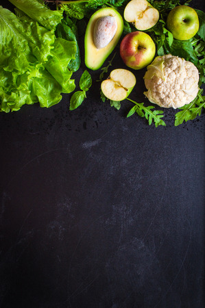 Fresh green vegetables and fruits on black chalk board background. ?auliflower, avocado, spinach, lettuce salad, green apples, herbs. Vegetarian food. Diethealthydetox food concept. Space for text