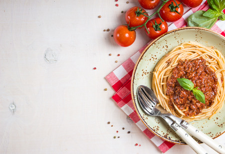 Italian pasta bolognese. Spaghetti with meat and tomato sauce in a plate with Italian tablecloth on a wooden white background. With fresh cherry tomatoes, basil. Food frame. Space for text. Top view