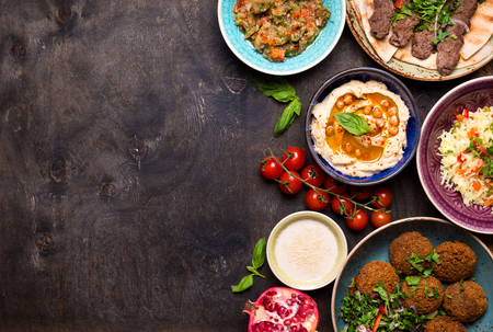 Middle eastern or arabic dishes and assorted meze on a dark background. Meat kebab, falafel, baba ghanoush, hummus, rice with vegetables, tahini, kibbeh, pita. Halal food. Space for text. Top view Stock Photo