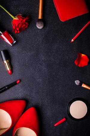 Fondo negro cosmético de la belleza. Esencial de maquillaje. Zapatos, lápiz labial rojo, polvo, cepillos conjunto. Productos cosméticos. Vista superior. Fondo femenino o de la manera. Productos cosméticos. Productos de belleza. Mujer moderna