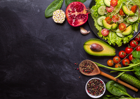 Ingredients for making salad on rustic black chalk board background. Vegetable salad in bowl, avocado, tomato, cucumber, spinach. Healthy, clean eating concept. Vegan or gluten free diet. Copy space