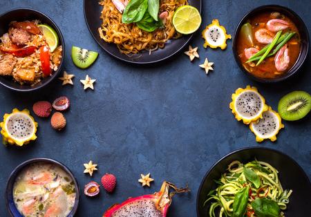 Thai food background. Dishes of thai cuisine. Tom yum, tom kha gai, pad thai noodles, thai fried rice with pork and vegetables khao phat mu, green papaya salad som tam, thai fruits. Space for text