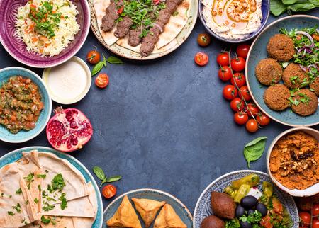Midden-Oosten of Arabische gerechten en diverse meze op concrete rustieke achtergrond. Vlees kebab, falafel, baba ghanoush, hummus, sambusak, rijst, tahin, kibbeh, pita. Halal eten. Ruimte voor tekst. bovenaanzicht Stockfoto - 71416988
