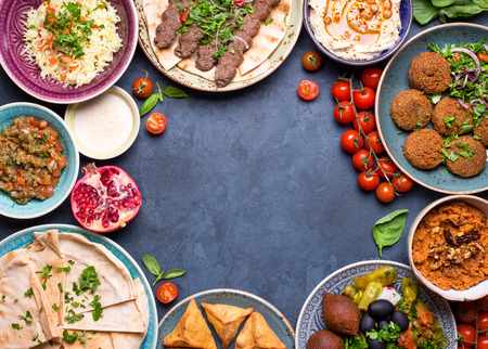 Middle eastern or arabic dishes and assorted meze on concrete rustic background. Meat kebab, falafel, baba ghanoush, hummus, sambusak, rice, tahini, kibbeh, pita. Halal food. Space for text. Top view