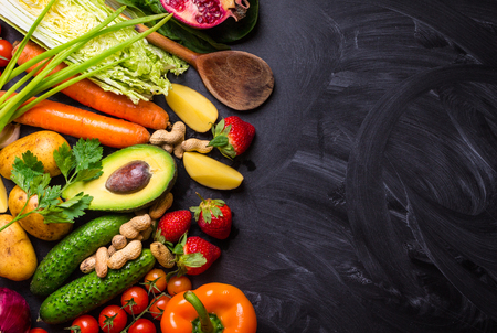 Vegetables, fruits, herbs, raw ingredients for cooking and spoon on rustic black chalk board background. Healthy, clean eating concept. Vegan or gluten free diet. Space for text. Top view. Food frame
