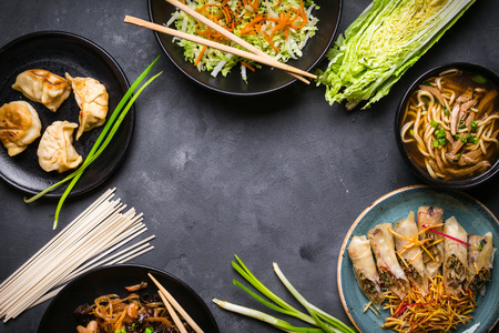 Chinese food dark background. Chinese noodles, fried rice, noodle soup, dim sum, spring rolls, salad. Traditional Chinese cuisine dishes set. Space for text. Top view. Chinese restaurant concept Foto de archivo