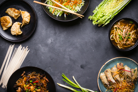 Chinese food dark background. Chinese noodles, fried rice, noodle soup, dim sum, spring rolls, salad. Traditional Chinese cuisine dishes set. Space for text. Top view. Chinese restaurant concept Stock Photo