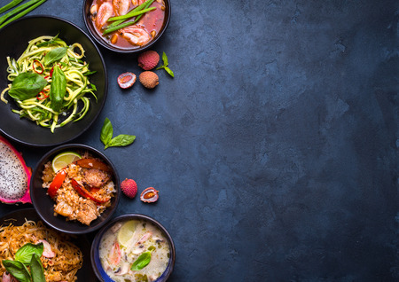 Thai food background. Dishes of thai cuisine. Tom yum, tom kha gai, pad thai noodles, thai fried rice with pork and vegetables khao phat mu, green papaya salad som tam, thai fruits. Space for text