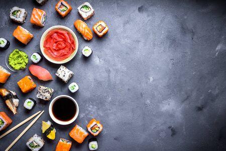 素朴な暗い背景に日本の寿司。巻き寿司、握り寿司、マキ、紅生姜、わさび、醤油寿司のテーブルにセットします。テキストのためのスペース。平