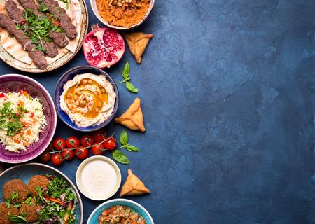Midden-Oosten of Arabische gerechten en diverse meze op concrete rustieke achtergrond. Vlees kebab, falafel, baba ghanoush, hummus, sambusak, rijst, tahin, kibbeh, pita. Halal eten. Ruimte voor tekst. bovenaanzicht