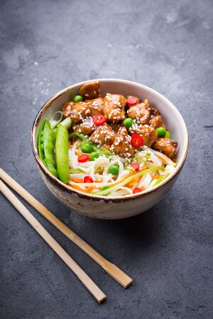 stir up: Asian style noodles with teriyaki chicken, vegetables and green peas pods. Noodles in bowl on rustic concrete background. Chinesethaijapanese style dish. Stir fry noodles. Close-up