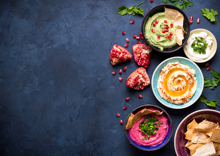 Colorful hummus bowls background. Different kinds of dips. Traditional hummus, herbs hummus, beetroot hummus, spread. Assorted meze and dips with crispy pita. Space for text. Meze and snacks concept Stock Photo