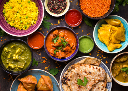 Assorted indian food on dark wooden background. Dishes and appetizers of indian cuisine. Curry, butter chicken, rice, lentils, paneer, samosa, naan, chutney, spices. Bowls and plates with indian food Foto de archivo