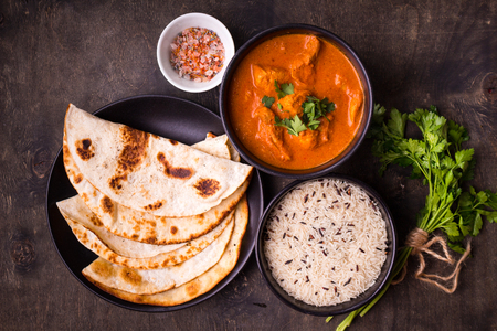 Hot spicy chicken tikka masala in bowl. Chicken curry with rice, indian naan butter bread, spices, herbs. Traditional Indian/British dish, popular indian curry in UK. Top view. Indian food. Close-up  스톡 콘텐츠