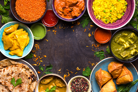Różne potrawy indyjskie na ciemnym tle drewnianym. Naczynia kuchni indyjskiej. Curry, masło kurczaka, ryż, soczewica, paneer, samosa, naan, chutney, przyprawy. Przestrzeń na tekst. Miska i talerze z indian żywności