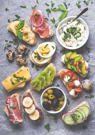 Assorted healthy sandwiches set background. Sandwich bar or buffet. Ciabatta sandwiches with dips, fish, cheese, meat, vegetables, fruits. Top view. Making sandwiches concept. Lunch time snacks Stock Photo
