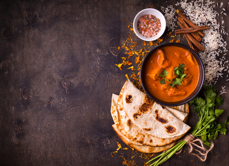Spicy chicken tikka masala in bowl on rustic wooden background. With rice, indian naan butter bread, spices, herbs. Space for text. Traditional IndianBritish dish. Top view. Indian food. Copy space
