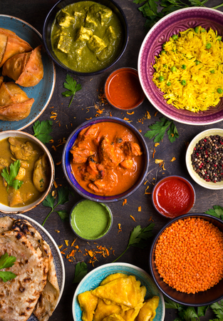 Assorted indian food on dark wooden background. Dishes and appetizers of indian cuisine. Curry, butter chicken, rice, lentils, paneer, samosa, naan, chutney, spices. Bowls and plates with indian food Banco de Imagens