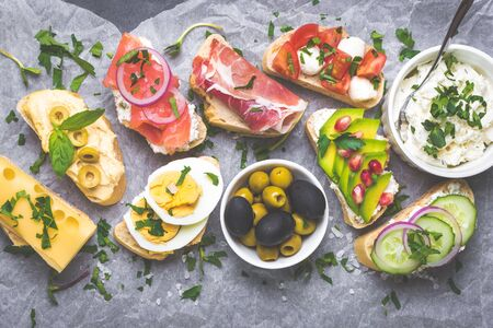 Assorted healthy sandwiches set background. Sandwich bar or buffet. Ciabatta sandwiches with dips, fish, cheese, meat, vegetables. Top view. Making sandwiches concept. Lunch time snacks. From above Stock Photo