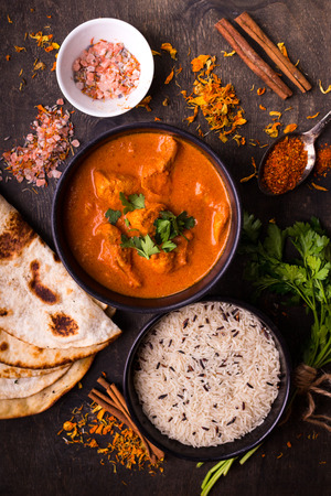 Hot spicy chicken tikka masala in bowl. Chicken curry with rice, indian naan butter bread, spices, herbs. Traditional IndianBritish dish, popular indian curry in UK. Top view. Indian food. Close-up  Фото со стока