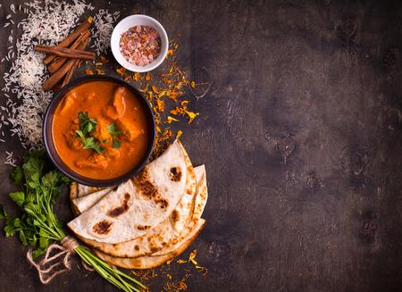 소박한 나무 배경에 그릇에 매운 닭 tikka masala. 쌀, 인도 naan 버터 빵, 향신료, 허브와 함께. 텍스트를위한 공간입니다. 전통적인 인도식  영국식 요리.