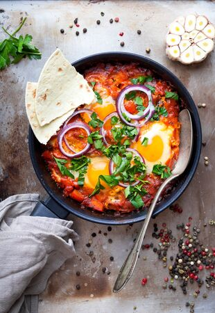 Shakshuka with pita bread in a pan. Middle eastern traditional dish. Fried eggs with tomatoes, bell pepper, vegetables and herbs. Shakshouka on a table. Top view. Sunny side up eggs. From above