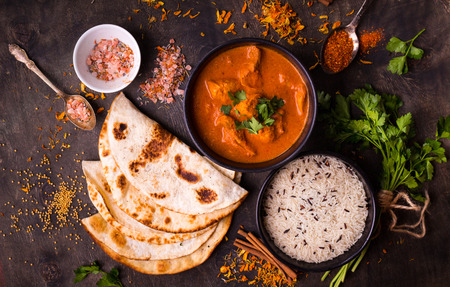 Hot spicy chicken tikka masala in bowl. Chicken curry with rice, indian naan butter bread, spices, herbs. Traditional Indian/British dish, popular indian curry in UK. Top view. Indian food. Close-up  Foto de archivo