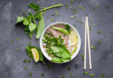 Traditional vietnamese noodle soup pho in bowl, garnished with basil, mint, lime, on concrete background. Vietnamese beef soup pho bo. Close-up. Asianvietnamese food. Vietnamese dinner. Pho bo meal Stock Photo