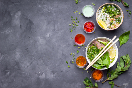 Traditional vietnamese noodle soups pho set: beef pho bo, chicken pho ga. Vietnamese soups in bowl. Asian/vietnamese food background. Space for text. Healthy vietnamese dinner. Top view. Copy space