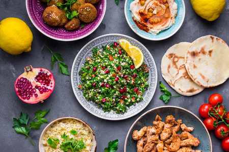 iraqi: Assorted middle eastern dishes and meze. Tabbouleh salad, meat shawarma, hummus bowl, falafel, pita, bulgur, pomegranate, lemons. Arab cuisine. Party food. Middle eastern dinner. Ethnic food. Top view Stock Photo