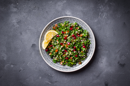 iraqi: Tabbouleh salad on plate, rustic concrete background. Traditional middle eastern or arab dish. Levantine vegetarian salad with parsley, mint, bulgur, tomatoes. Part of middle eastern meze. Top view