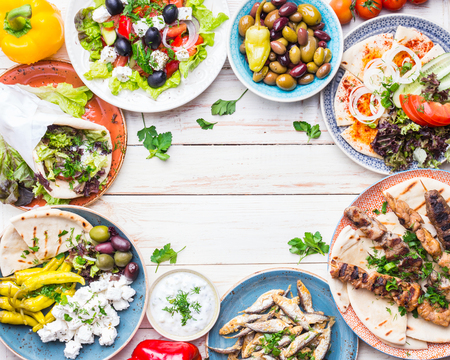 Greek food background. Meze, gyros, souvlaki, fried fish, pita, greek salad, tzatziki, assortment of feta, olives and vegetables. Traditional greek dishes set. Space for text. Top view. Food for share