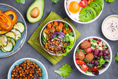 Mixed healthy vegetarian salads with vegetables, sweet potato, falafel, bulgur, avocado, eggs. Assorted buddha bowl salads. Vegetarian food. Healthy lunch/dinner. Salad in bowl. Ingredients for making