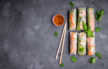 Fresh assorted spring rolls set background. Handmade asianChinese spring rolls, sauce, chopsticks. Rustic concrete background. Spring rolls with shrimps, vegetables, fruits. Space for text. Top view Stock Photo