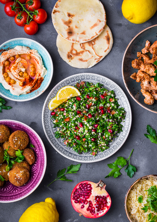 Assorted middle eastern dishes and meze. Tabbouleh salad, meat shawarma, hummus bowl, falafel, pita, bulgur, pomegranate, lemons. Arab cuisine. Party food. Middle eastern dinner. Ethnic food. Top view Stock Photo