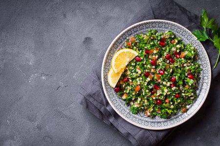 Tabbouleh salad, plate, rustic concrete background. Traditional middle eastern or arab dish. Levantine vegetarian salad with parsley, mint, bulgur, tomato. Part of middle eastern meze. Space for text Stock Photo