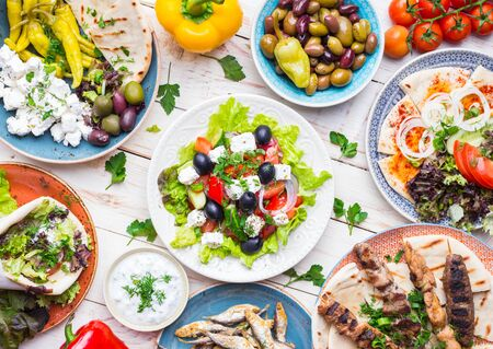 dipping: Greek food background. Meze, gyros, souvlaki, fish, pita, greek salad, tzatziki, assortment of feta, olives and vegetables. Traditional different greek dishes set. Top view. Food for share. Close-up