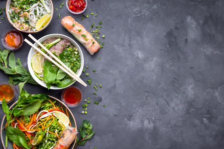 Assorted asian dinner, vietnamese food. Vietnamese noodle soup pho bo, pho ga, spring rolls, vegetable salad. Asianvietnamese food background. Copy space. Traditional vietnamese dishes set. Top view Stock Photo