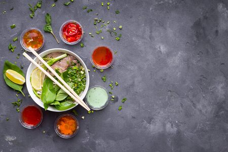 Traditional vietnamese noodle soup pho in bowl with assorted sauces on concrete background. Vietnamese beef soup pho bo. Asian/vietnamese food background. Space for text. Healthy vietnamese dinner Stok Fotoğraf