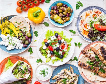 Greek food background. Meze, gyros, souvlaki, fish, pita, greek salad, tzatziki, assortment of feta, olives and vegetables. Traditional different greek dishes set. Top view. Food for share. Close-up