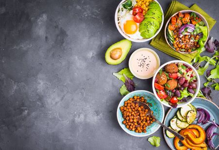 dipping: Mixed healthy vegetarian salads with vegetables, sweet potato, falafel, bulgur, avocado, eggs. Assorted buddha bowl salads background. Healthy dinner. Salad in bowl. Making ingredients. Space for text Stock Photo