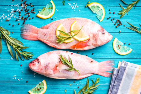 Fresh fish tilapia ready to cook. Raw fish with herbs, lemon, salt, pepper on wooden rustic background. Ingredients for cooking or making healthy dinner. Diethealthy eating concept. Preparing fish
