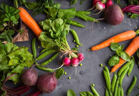 Fresh vegetables on rustic concrete background. Carrot, beet, radish, green pea, herbs. Harvest/gardening concept. Healthy food. Vegetarianism. Clean eating. Top view. Making salad ingredients