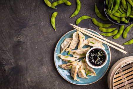 Chinese dumplings on plate, green boiled soybeans edamame, soy sauce and chopsticks background. Traditional ChineseAsian dish. Dim sum dumplings ready to eat. Chinese cuisine concept. Space for text